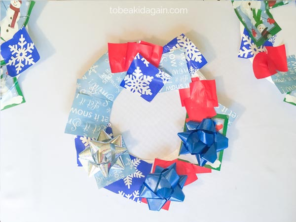 Winter Craft for kids using recycled wrapping paper and bows for a winter wreath paper college. Great for scissor skill and fine motor practice for preschoolers